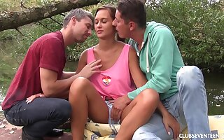 Outdoor MMF threesome with blonde sporty teen on a raft